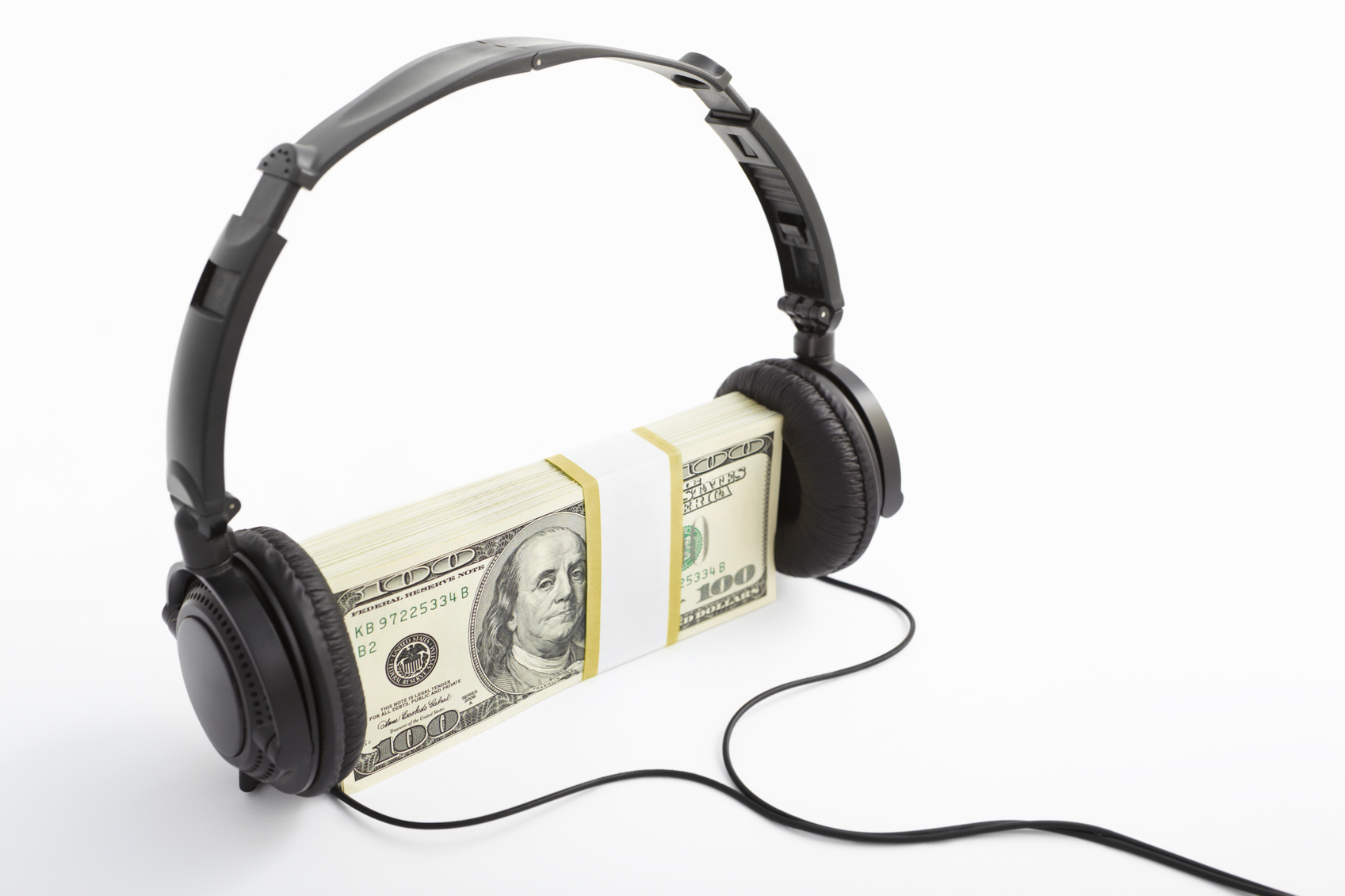 A stack of US$100 bills with headphone put on, over white background