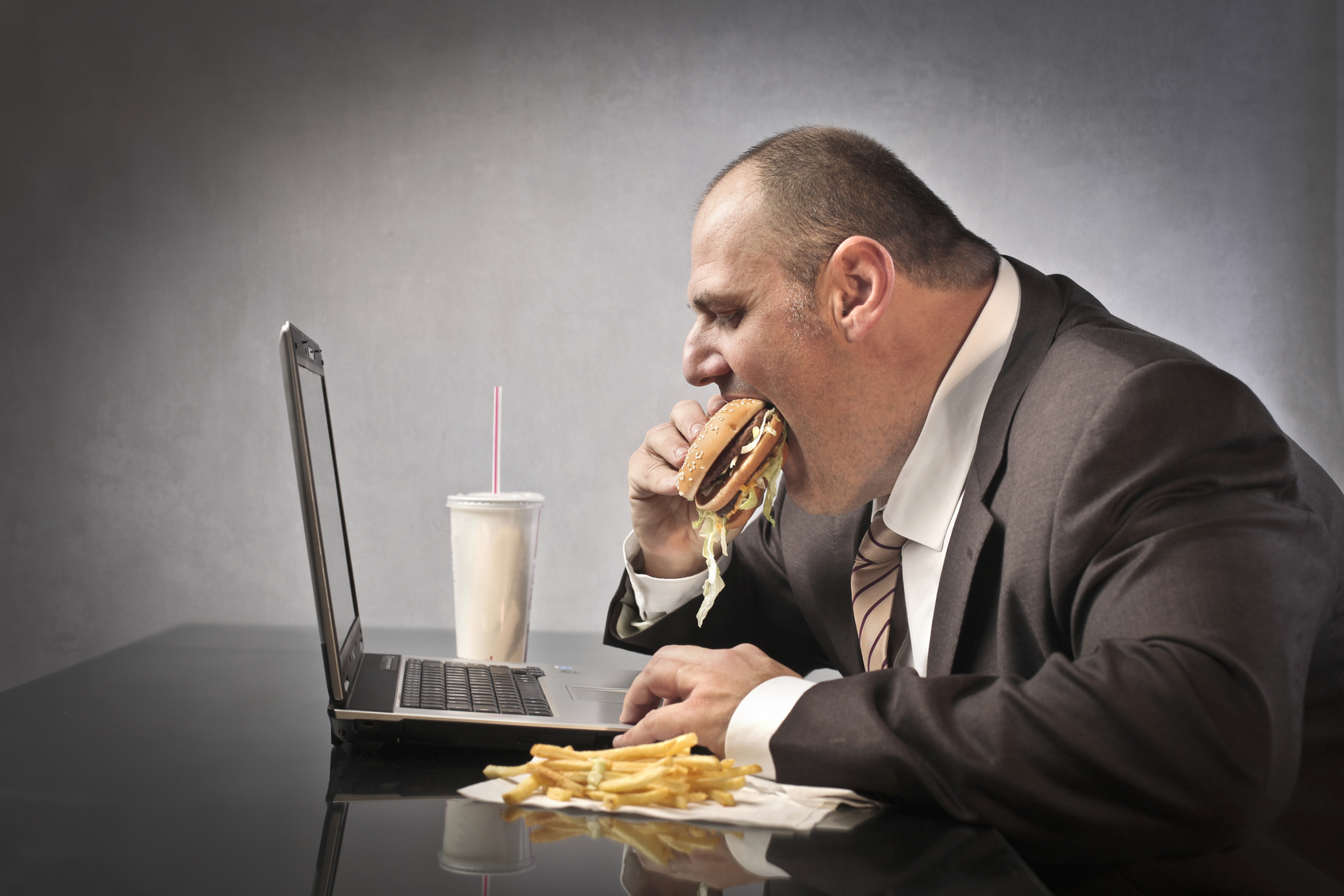 Fat businessman eating junk food in front of a laptop
