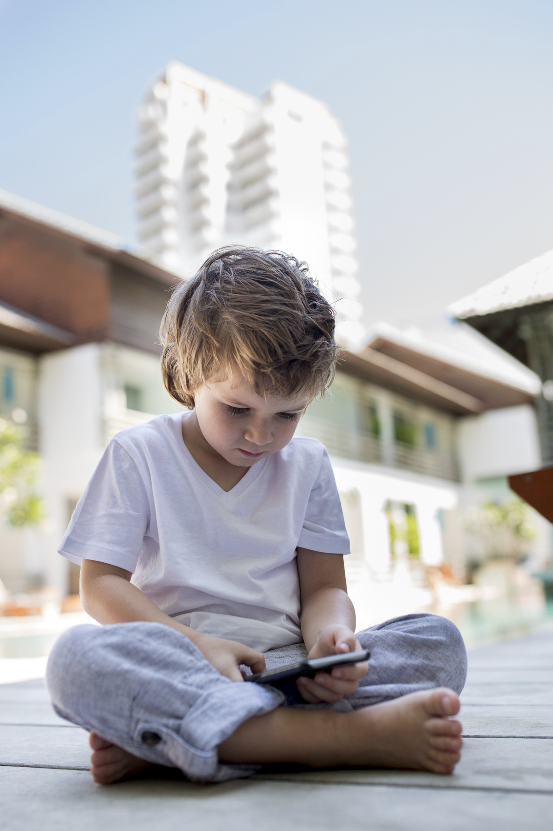 Small kid sitting on a floor outside and using cell phone.