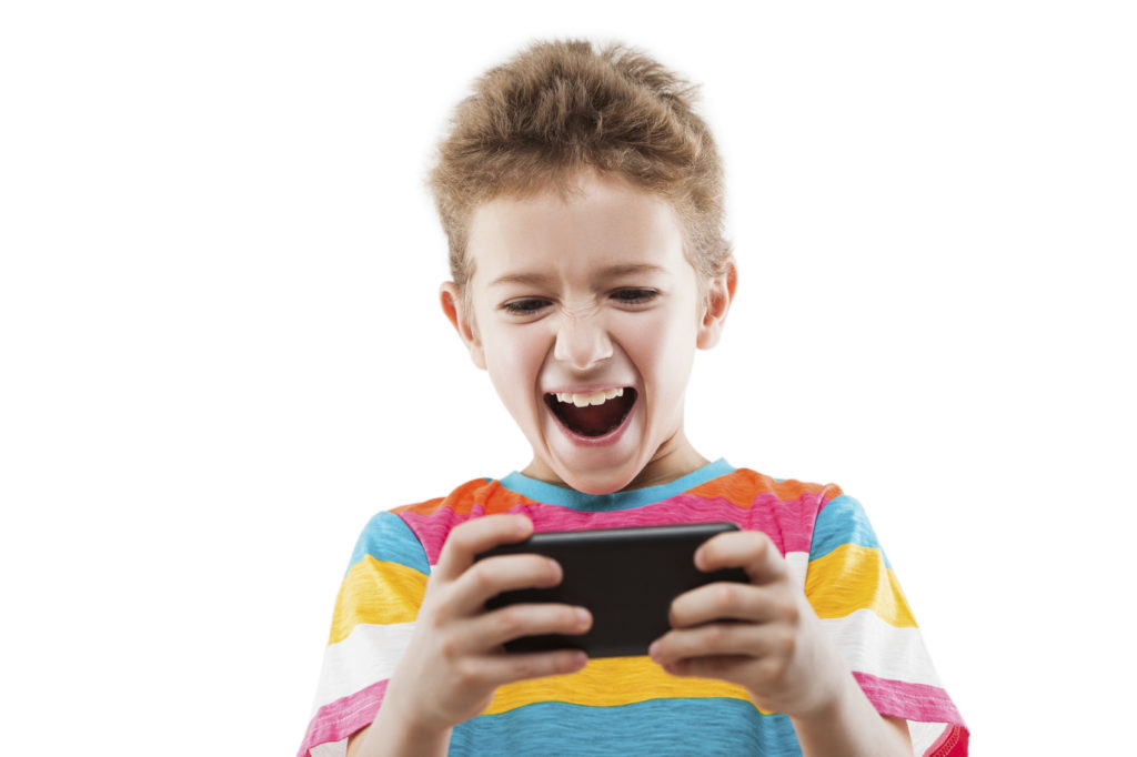 Smiling child boy playing games or surfing internet on smartphone