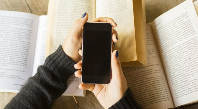 Girl with cell phone and books