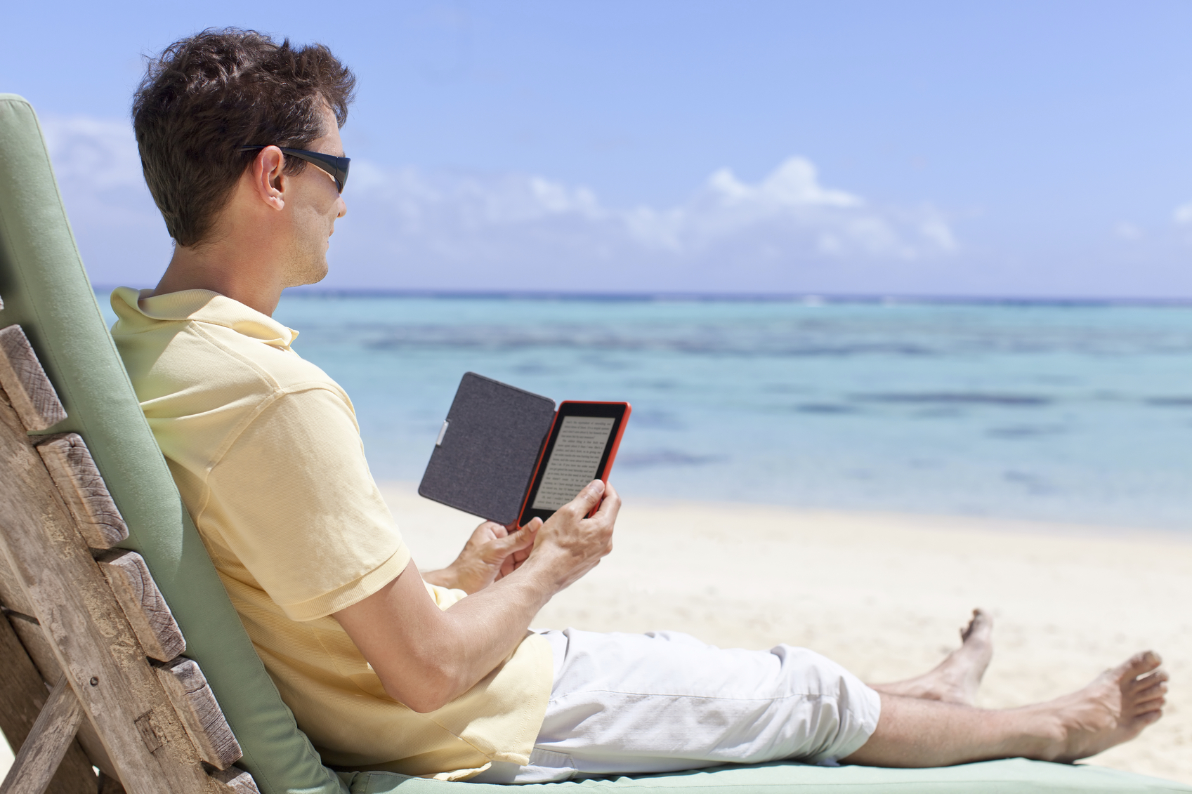 handsome man at the beach reading his electronic reader