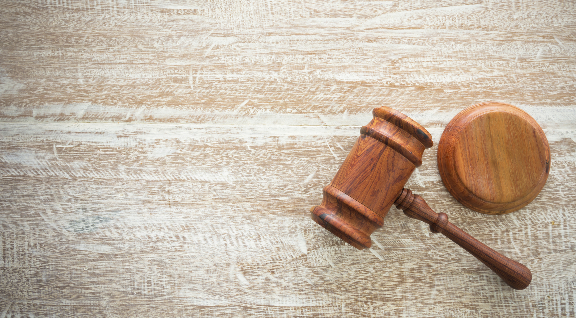 wooden judges gavel and soundboard resting on top of wooden desk.