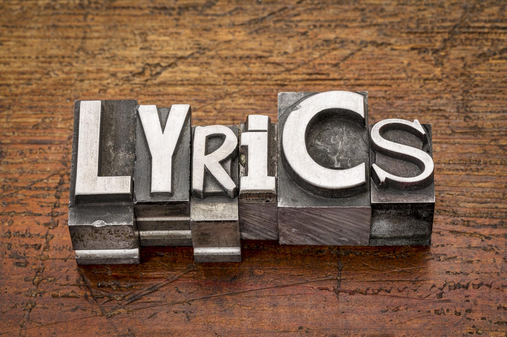 lyrics word in mixed vintage metal type printing blocks over grunge wood