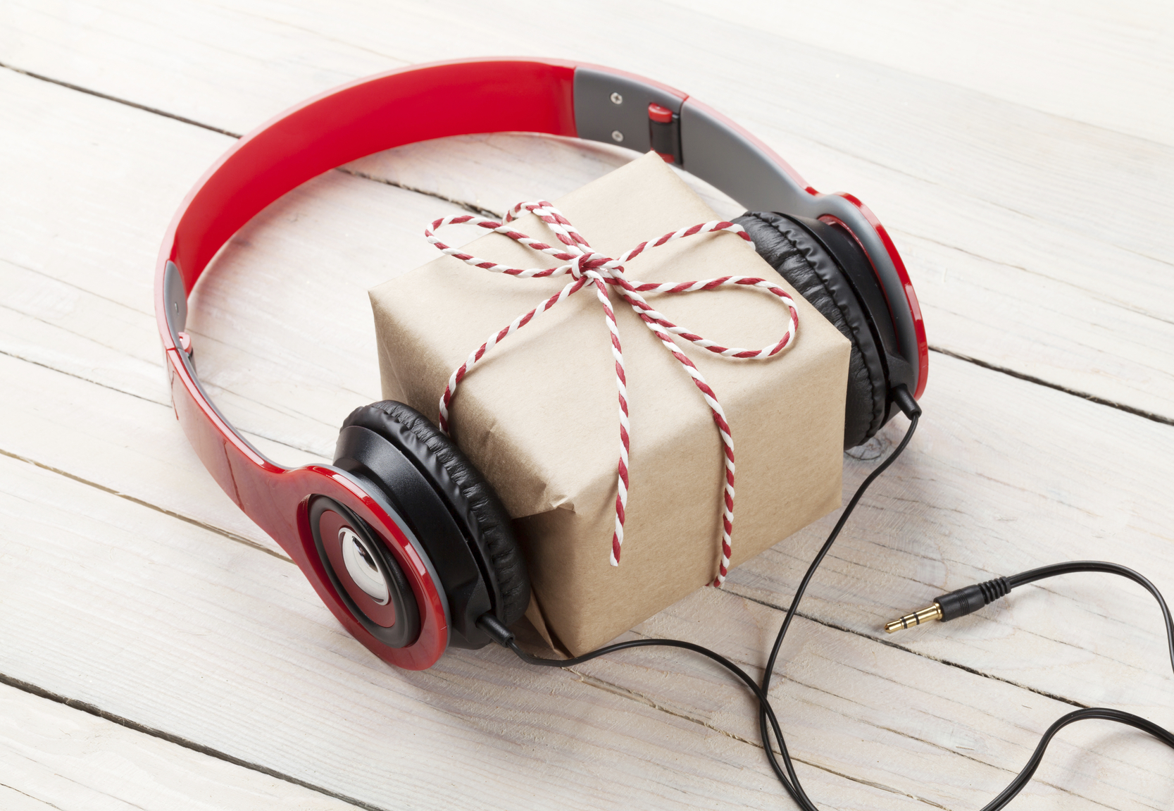 Gift box with headphones on wooden table