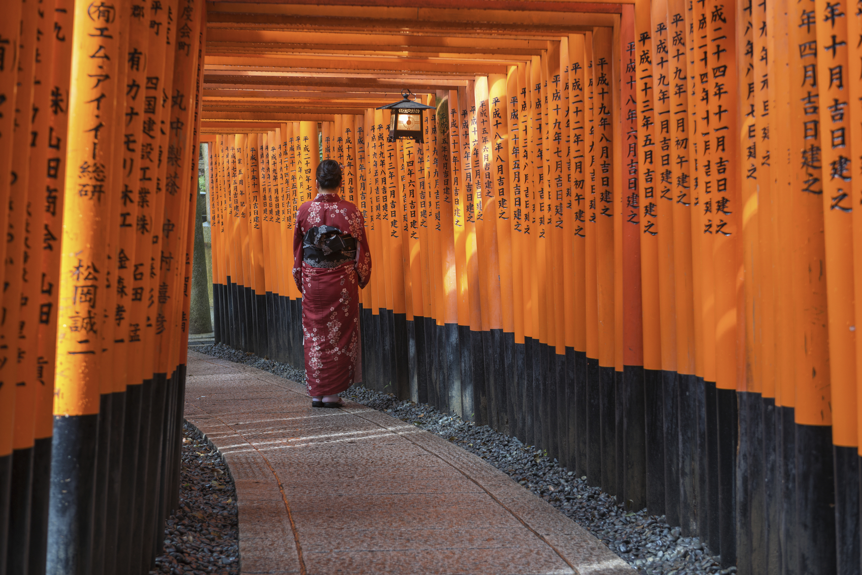 Kyoto, Japan - February 6, 2013: Women in kimono stand alone at Red Torii gates in Fushimi Inari shrine, one of famous landmarks in Kyoto, Japan