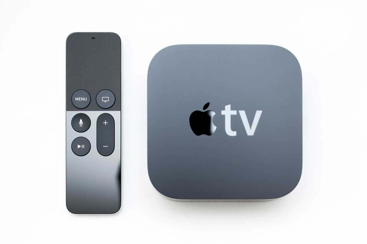 Paris, France - November 10, 2015: Focus on the remote control of the New Apple TV media streaming  player microconsole by Apple Computers next to the new touch remote swipe-to-select with integrated Siri and motion sensor on white