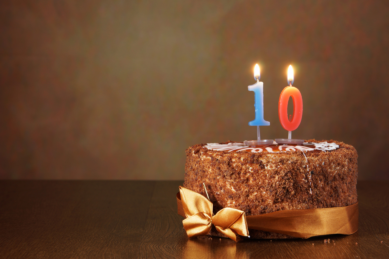 Birthday chocolate cake with burning candle as a number ten