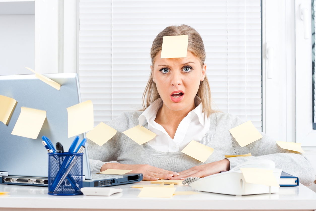 An overworked woman with sticky notes all over her and desk