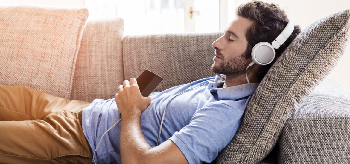 Man on his sofa listening to music with a smartphone
