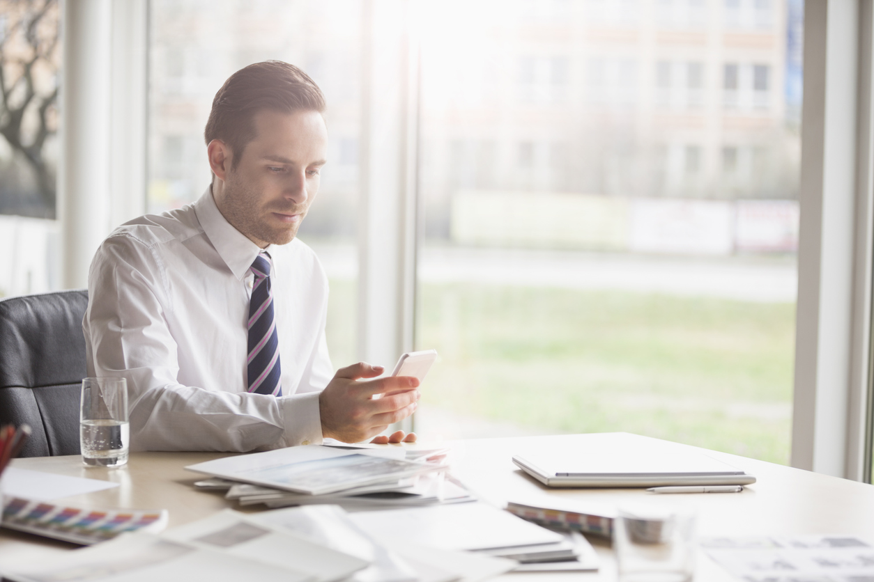 Young businessman using mobile phone at office desk