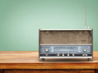 Old retro radio on table with vintage green eye light background