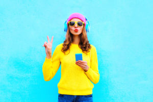 Fashion pretty woman listening music in headphones with smartphone colorful