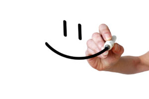 Hand draws smiley with black marker on transparent whiteboard