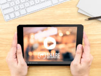 Hand holding tablet with Video sharing on screen on table