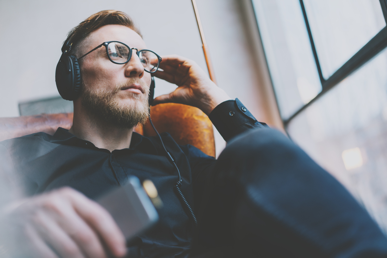 Portrait handsome bearded man glasses,headphones listening to music modern