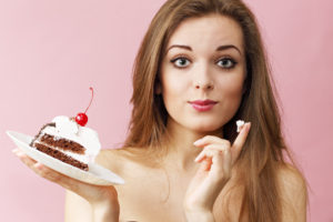 Woman eating the cream from a cream cake