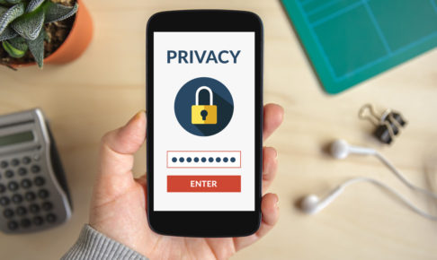 Hand holding smart phone with online privacy concept on screen