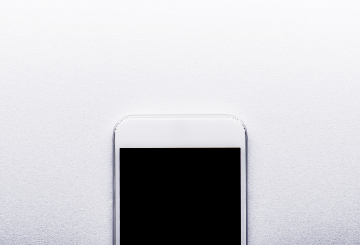 Smart phone laid on white office desk, copy space