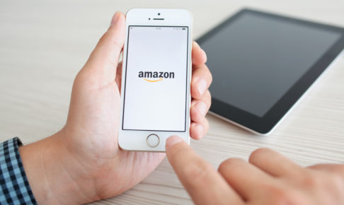 man holding iPhone 5s with app Amazon on the screen