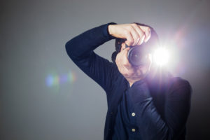 Photographer takes picture in studio using flash
