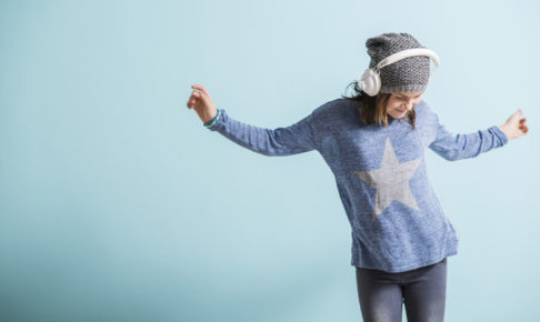 Girl with head phones dancing and listening to music