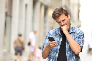 furious angry man watching mobile phone