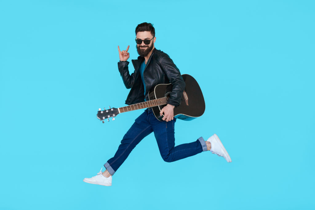 Man guitar player jumps while showing rock gesture