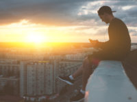 Man sitting on the edge of the roof with smartphone