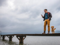 Man standing on dock and using smart phone