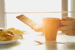 Fresh Breakfast with Hot Coffee, and Holding Smartphone in Morning Sunlight.