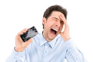 Angry man showing broken smartphone