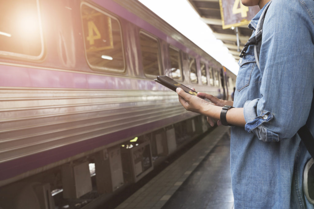 woman holding smartphone with backpack at train station