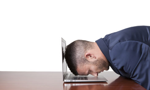 Businessman laying his head down on his laptop