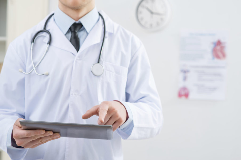 Professional doctor holding tablet
