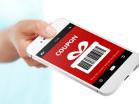 hand holding mobile phone with christmas coupon over white