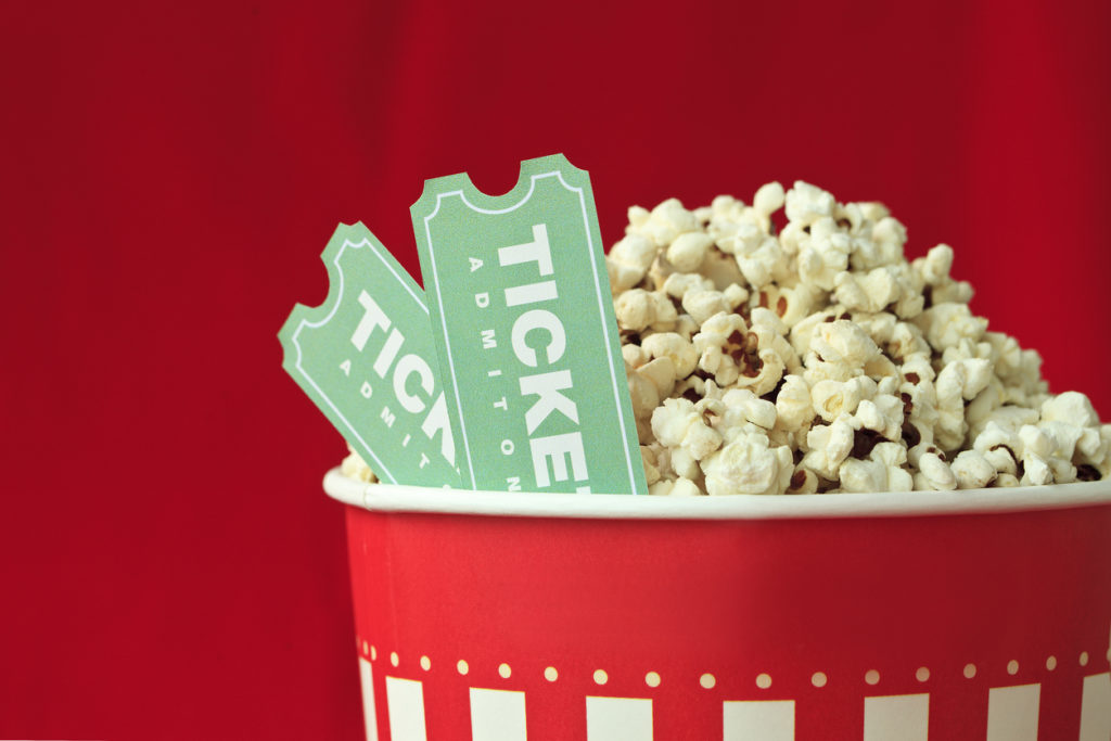 Popcorn Bag And Movie Ticket On Red Background