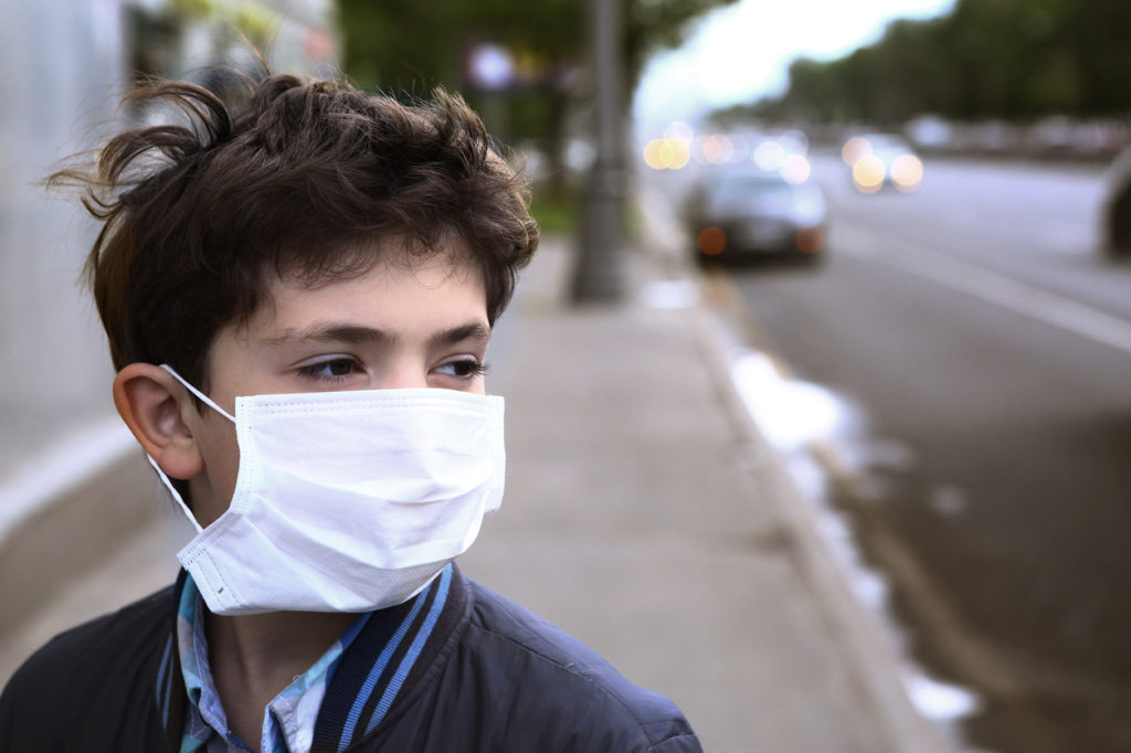 teenager boy in protection mask on the highway city