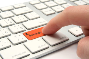 Finger pressing orange download button on a white keyboard