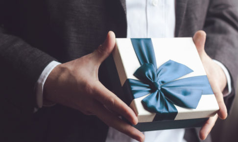 Man in suit offering gift with blue ribbon