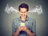 Frustrated angry man reading a text message on his smartphone blowing steam coming out of ears