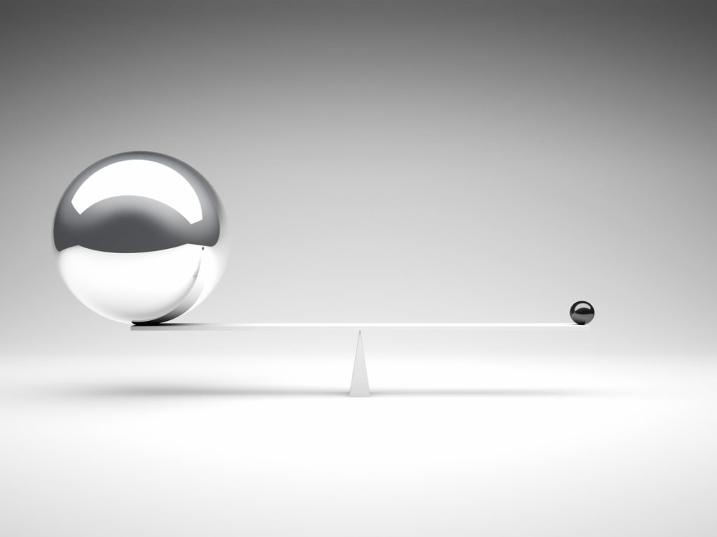 Two metal balls balancing on a white balance beam
