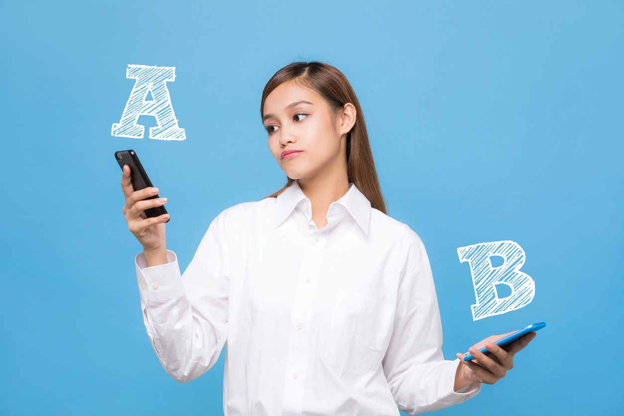 Young woman comparing smartphone A with smartphone B.