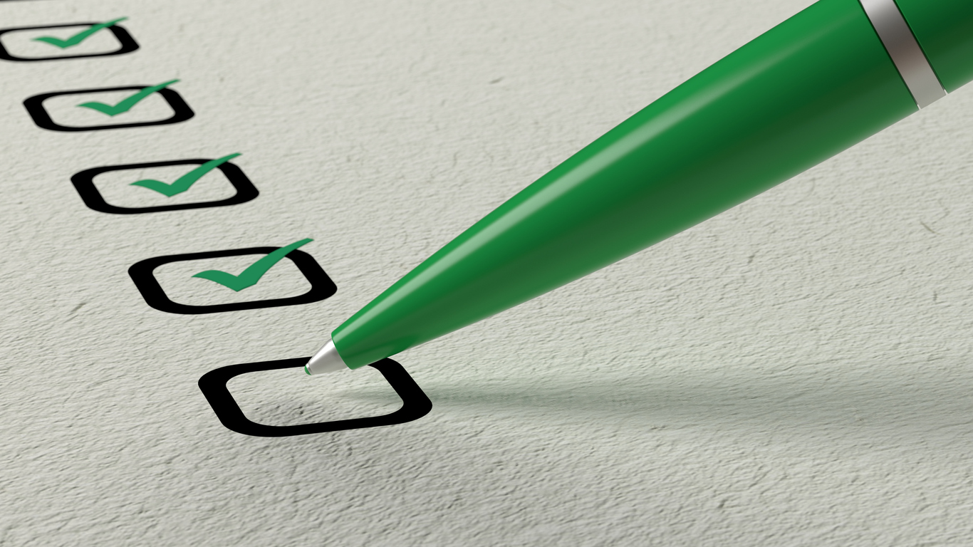 Green ball pen crossing off items from a checklist