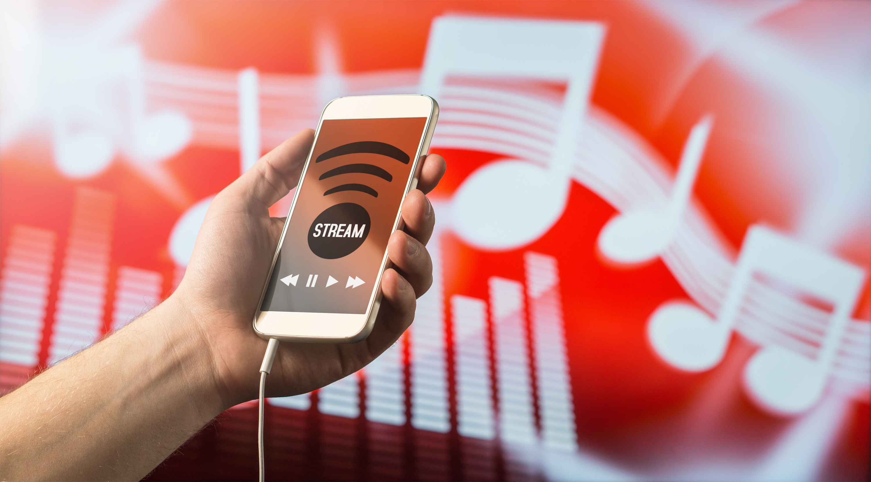Modern online music streaming concept. Close up of a man holding smartphone in hand and listening to music with mobile app. Red blurred note background.