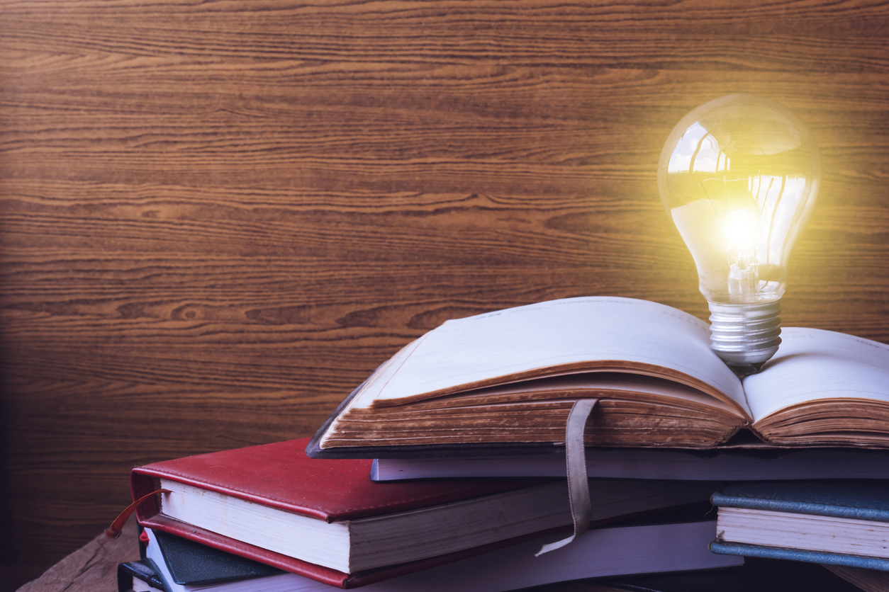 Open book with light bulb and hardback books on wood wall background. Free space for text. Selective focus