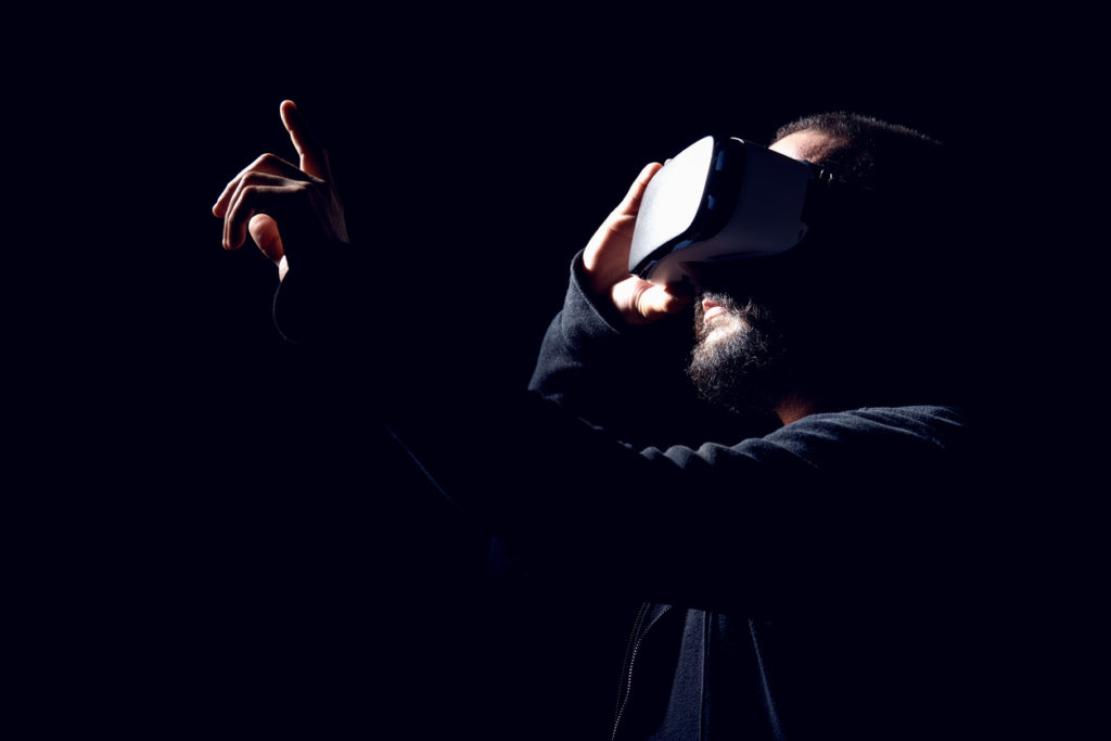 Hipster man wearing virtual reality goggles. Black background VR concept.