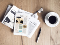 Newspaper with tablet on wooden table