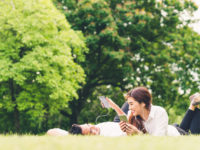 Young Asian lovely couple or college students listening to music together in the garden, with copy space. Leisure activity, Love relationship, wedding, or relaxing casual lifestyle concept