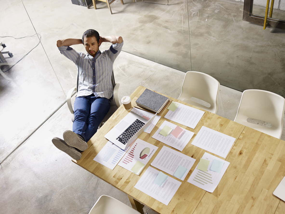 asian businessman sitting alone in office thinking